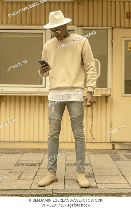 cool stylish man using smartphone at street, in Munich, Germany