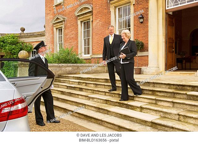 Caucasian butler holding car door for business people outside mansion