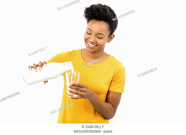 Portrait of smiling young woman pouring milk in a glass in front of white background