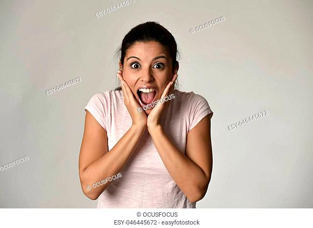 head portrait of young beautiful Spanish surprised woman amazed in shock and surprise happy and excited isolated grey background in astonished wow face...