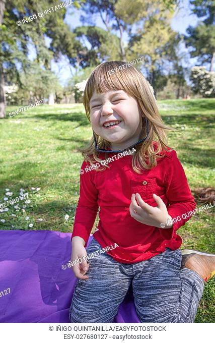 funny portrait of blonde three years old child, with red shirt sitting in green grass in park, laughing and playing with adult woman black oversize sunglasses
