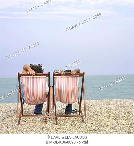 Couple relaxing in lounge chairs at the beach