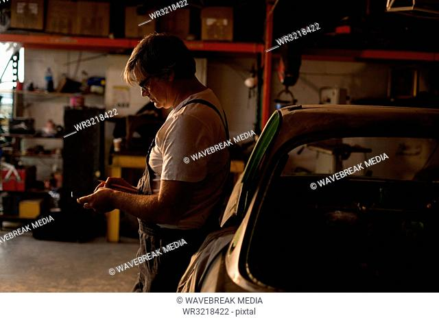 Male mechanic using mobile phone
