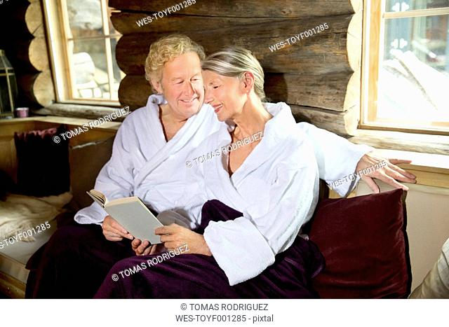 5db07a4fca Smiling senior couple sitting on bench in bathrobes reading a book