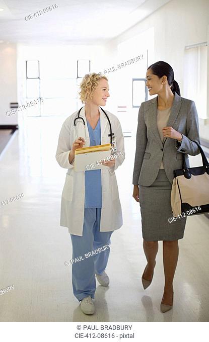 Doctor and businesswoman walking in hospital corridor