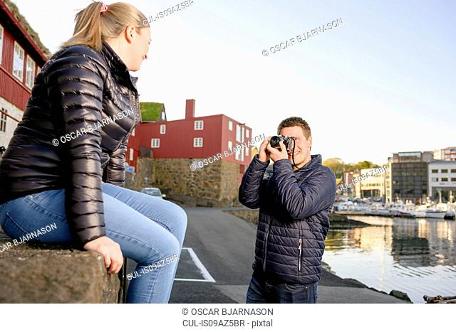 Young man photographing young woman,Tinganes, Torshavn, Faroe Islands