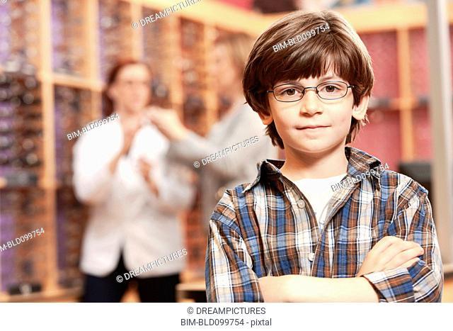 Caucasian boy standing in eyeglasses store
