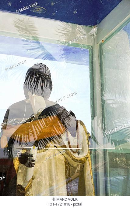 Religious statue seen through glass