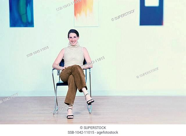 Portrait of a young woman sitting on a chair