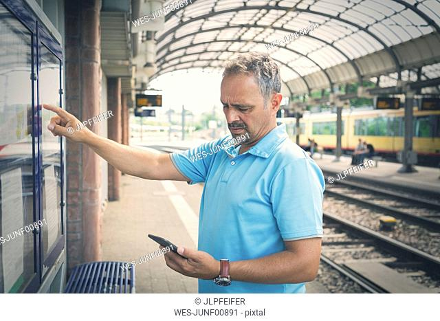 Man with smartphone standing on platform in front of timetable