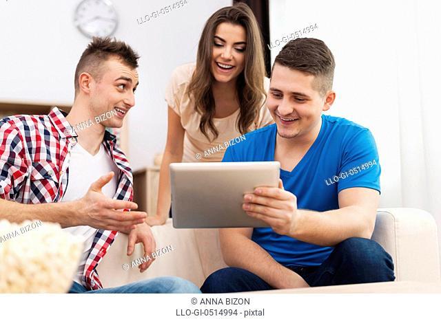 Friends enjoying free wifi on digital tablet. Debica, Poland