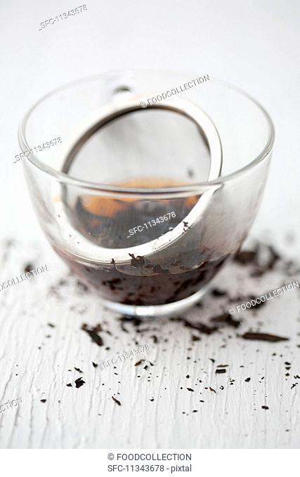A tea strainer with black tea