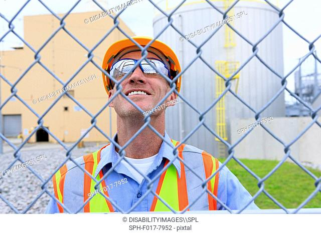 Engineer at electric power plant inside secured fence looking at power plant buildings