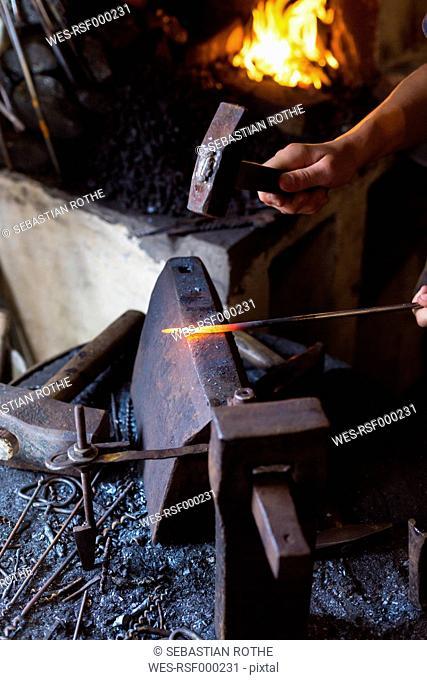 Blacksmith finishing work piece on an anvil
