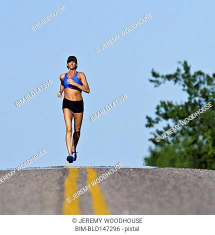 Caucasian runner training on remote road