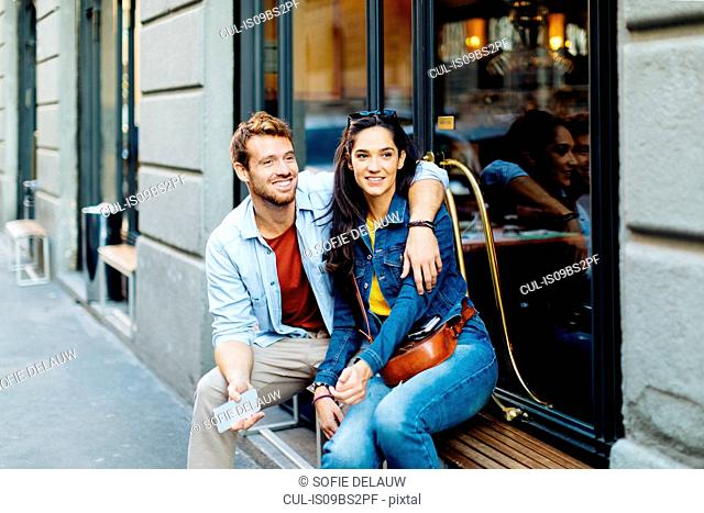 Couple sitting by shop window, Milan, Italy
