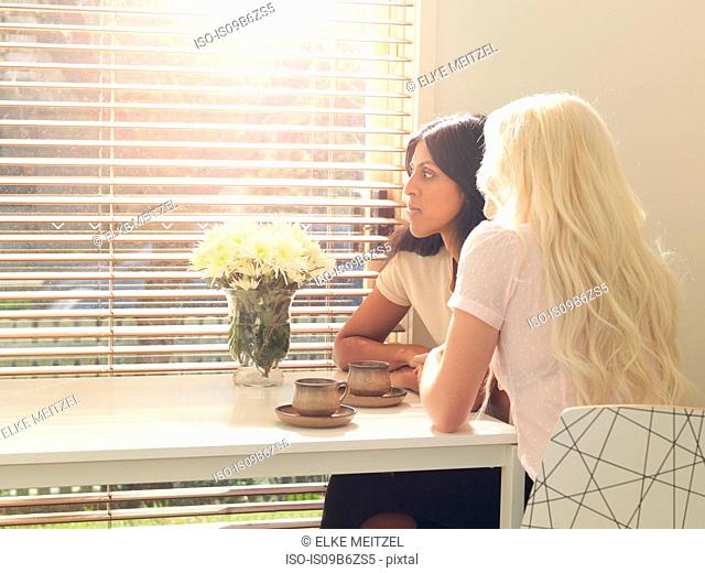Female friends sing at table, coffee cups on table in front of them