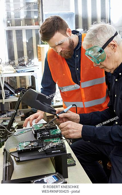 Workers in computer recycling plant dismantling hard disk