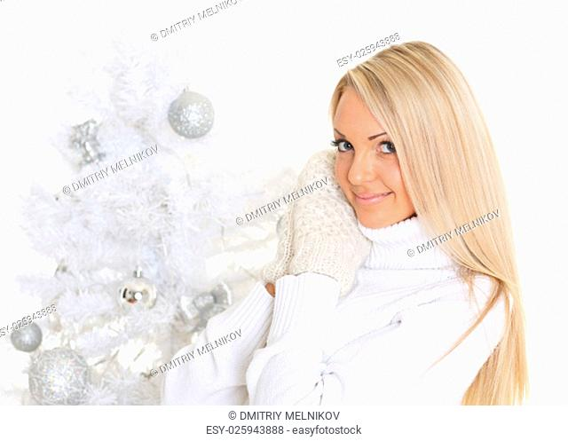 Young happy beautiful woman in winter clothes stands near Christmas tree on a white background