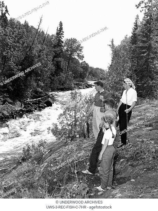 Oba, Ontario: c. 1958.A vacationing family from New York with a catch of speckled trout from the stream