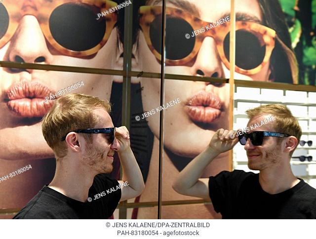 Max Frank, employee at 'Ace and Tate', tries on glasses in the flagship store of the Dutch glasses brand 'Ace and Tate' in Neue Schonhauser Strasse in Berlin