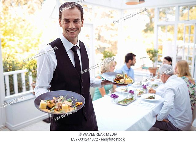 Portrait of smiling waiter holding food tray