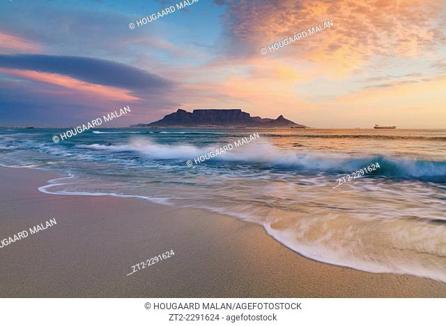 Wide angle landscape photo of a wave washing over a beach in sunset light with table mountain in the background. Bloubergstrand, Cape Town, South Africa