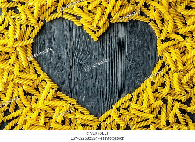 Heart shape made of fusilli. Italian cuisine. Horizontal view