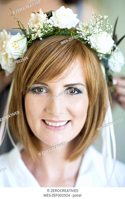 Portrait of smiling young woman wearing floral hair wreath