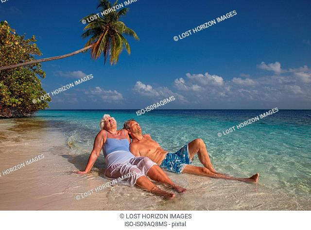 Senior couple relaxing on beach, Maldives