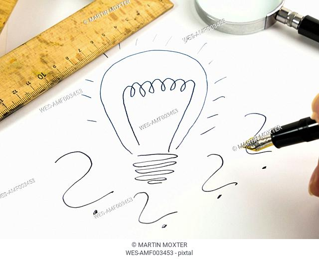 Drawn lightbulb and question marks on white paper