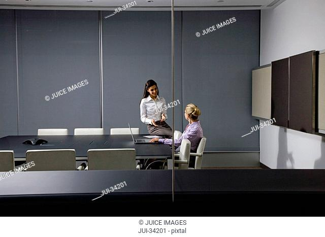 Businesswomen with laptop talking in conference room