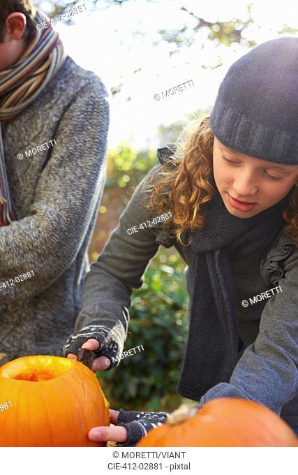 Children carving pumpkins together outdoors