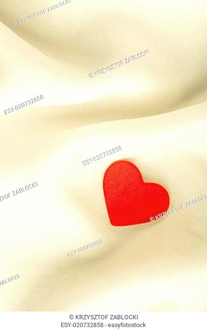 Red wooden decorative heart on white silk background