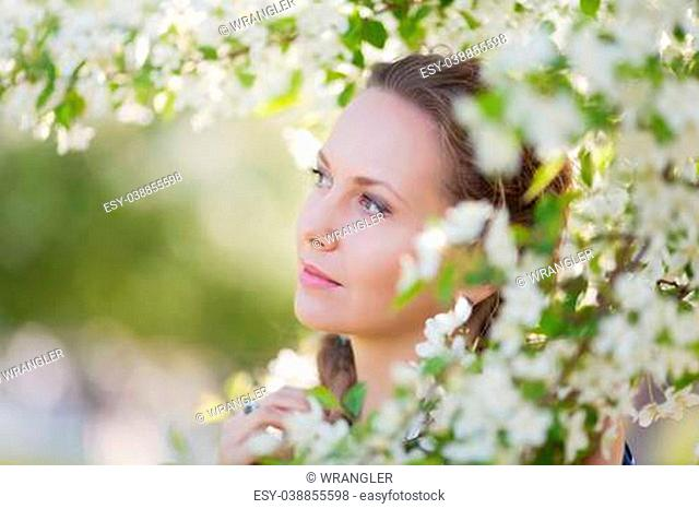 Portrait of young beautiful woman among blossoming trees