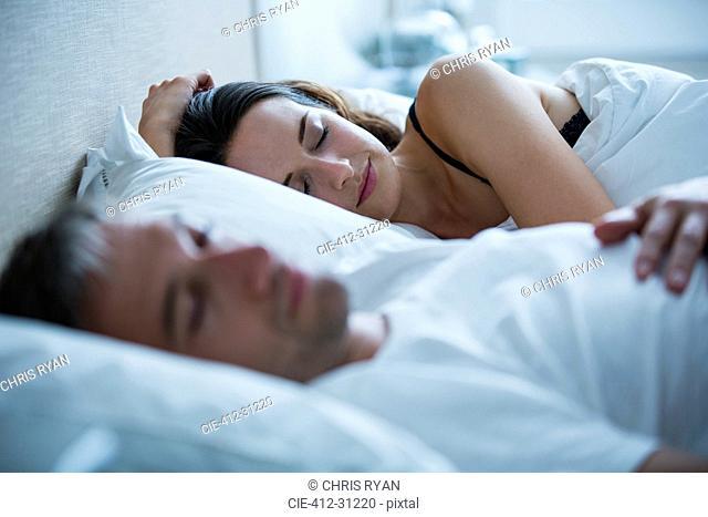 Serene couple sleeping in bed