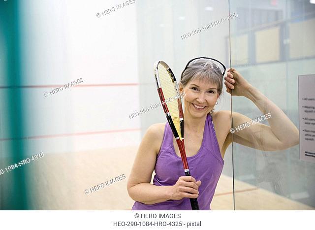 Portrait of smiling woman holding squash racket