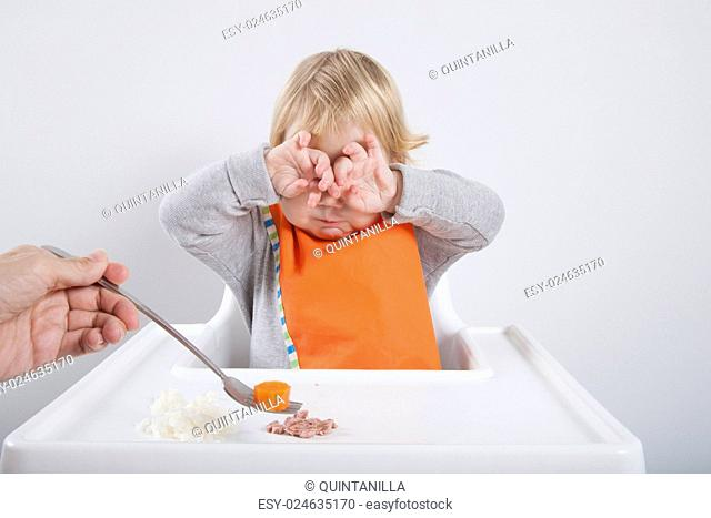 blonde caucasian baby seventeen month age orange bib grey sweater eating meal in white high-chair with hands on eyes does not like carrot
