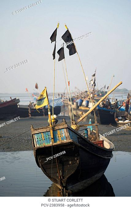 Fishing boat sits in water on the shore; Sittwe, Rakhine State, Burma