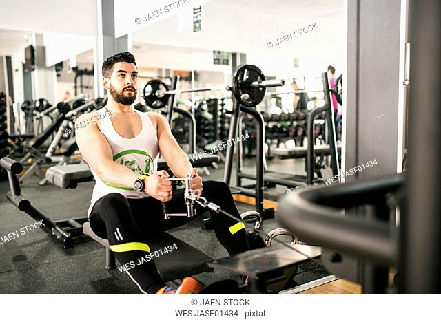 Man exercising with rowing machine in gym