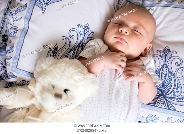 Baby sleeping on bed with teddy bear in bedroom