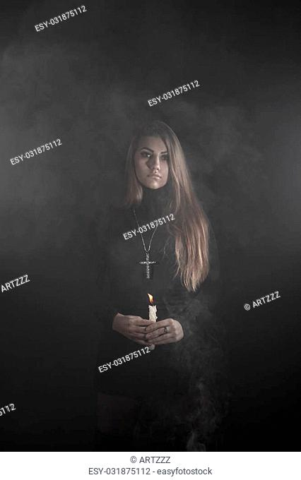 Lonely young woman holding a candle in a smoke