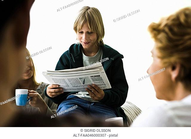 Boy reading newspaper, family members in foreground