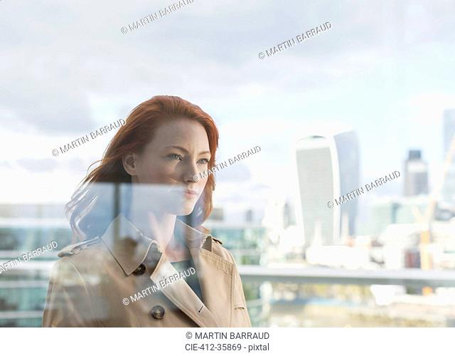 Confident businesswoman with red hair on urban balcony with city view