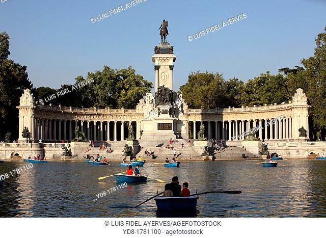 Tourists enjoying the boats in Retiro Park Pond with its monument and statue of Alfonso XII, Madrid, Spain, Europe