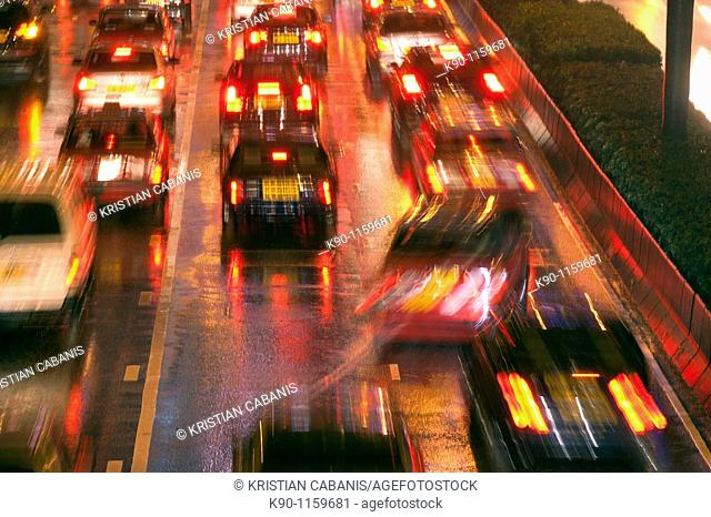 Blurred image of a traffic jam with cars seen from behind with their red lights and reflections on the wet street after a heavy rain at night, Central
