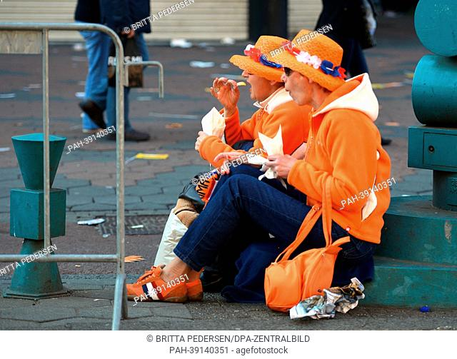 Two Oranje fans enjoying a meal on the occasion of the investiture of the country's new King, in Amsterdam, The Netherlands, 30 April 2013