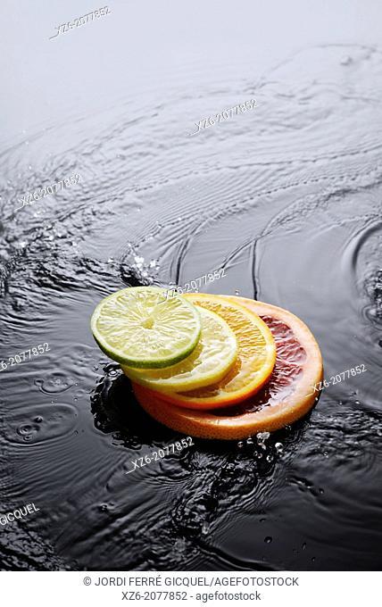 Citrus fruits, grapefruit, orange, lemon and lime slices splashing in water on black background