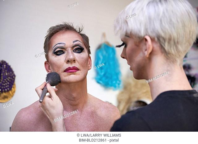 Caucasian drag queen applying colleague's makeup in bathroom