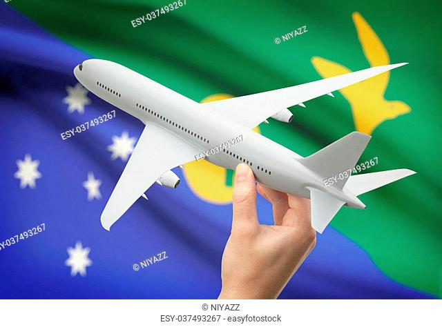 Airplane in hand with national flag on background - Christmas Island